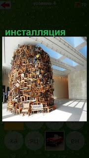 сделана инсталляция в помещении под потолок из разных вещей