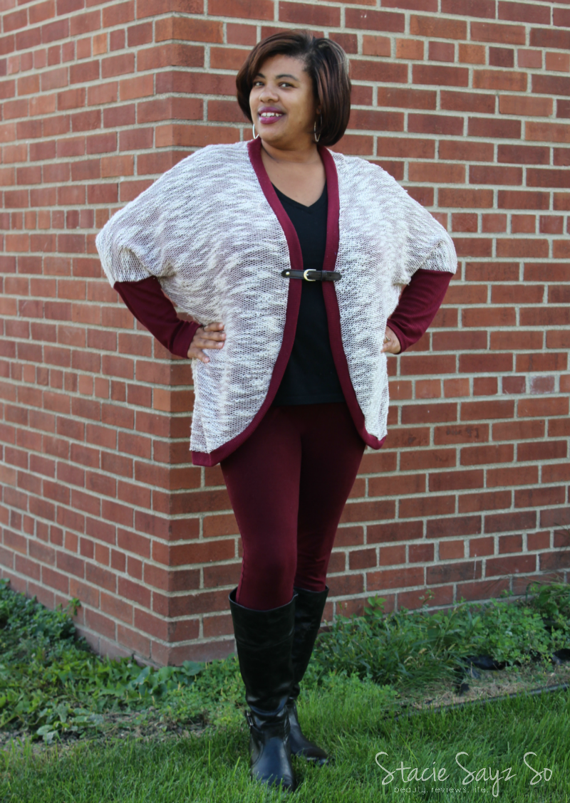 a woman wearing a sweater with burgundy leggings