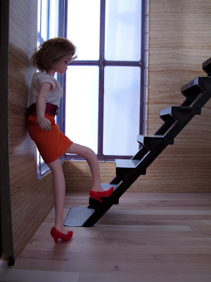 A doll at the bottom of the stairs of the modern Lori Loft to Love dolls' house.