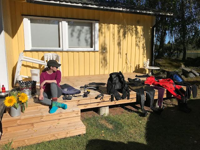 Henkilö istuu mökin terassilla, jolle on levitelty kuivumaan valtavasti sukellusvarusteita