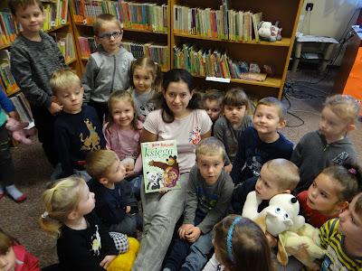 Przedszkolaki i biliotekarka pozują do zdjęcia. Bibliotekarka trzyma książkę o Maszy i Niedźwiedziu