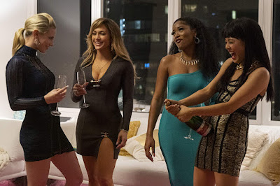 Movie still for Hustlers where Lili Reinhart, J. Lo, Keke Palmer, and Constance Wu drink champagne and laugh in a fancy New York Upper East Side apartment