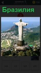 На высокой горе стоит статуя с раскинутыми руками, символ Бразилии. Внизу виден город с домами и дорогами