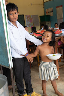 Boy hugs is sister and she holds his hand. She is super happy to be receiving his lunch. He looks satisfied that he could make her happy.