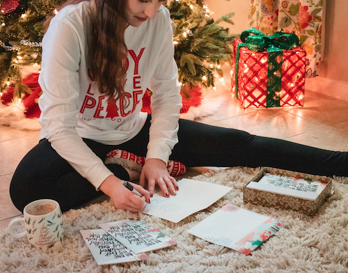 Madalyn sitting on floor in front of Christmas tree writing on Christmas card with cards scattered around and a mug sitting nearby.