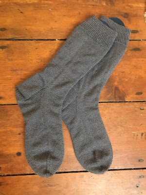 A pair of grey socks lying on some floorboards.