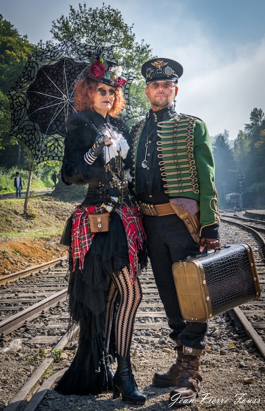 Man and woman dress in coordinating colorful steampunk costumes in red, black and green. Steampunk couples costumes.