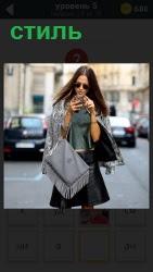 на улице девушка в стильной одежде с телефоном в руках