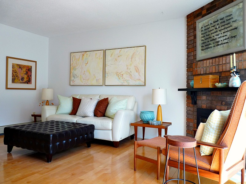 Living room with cream sofa, brick fireplace and mid-century teak