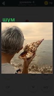 мужчина держит раковину и слушает шум моря на берегу