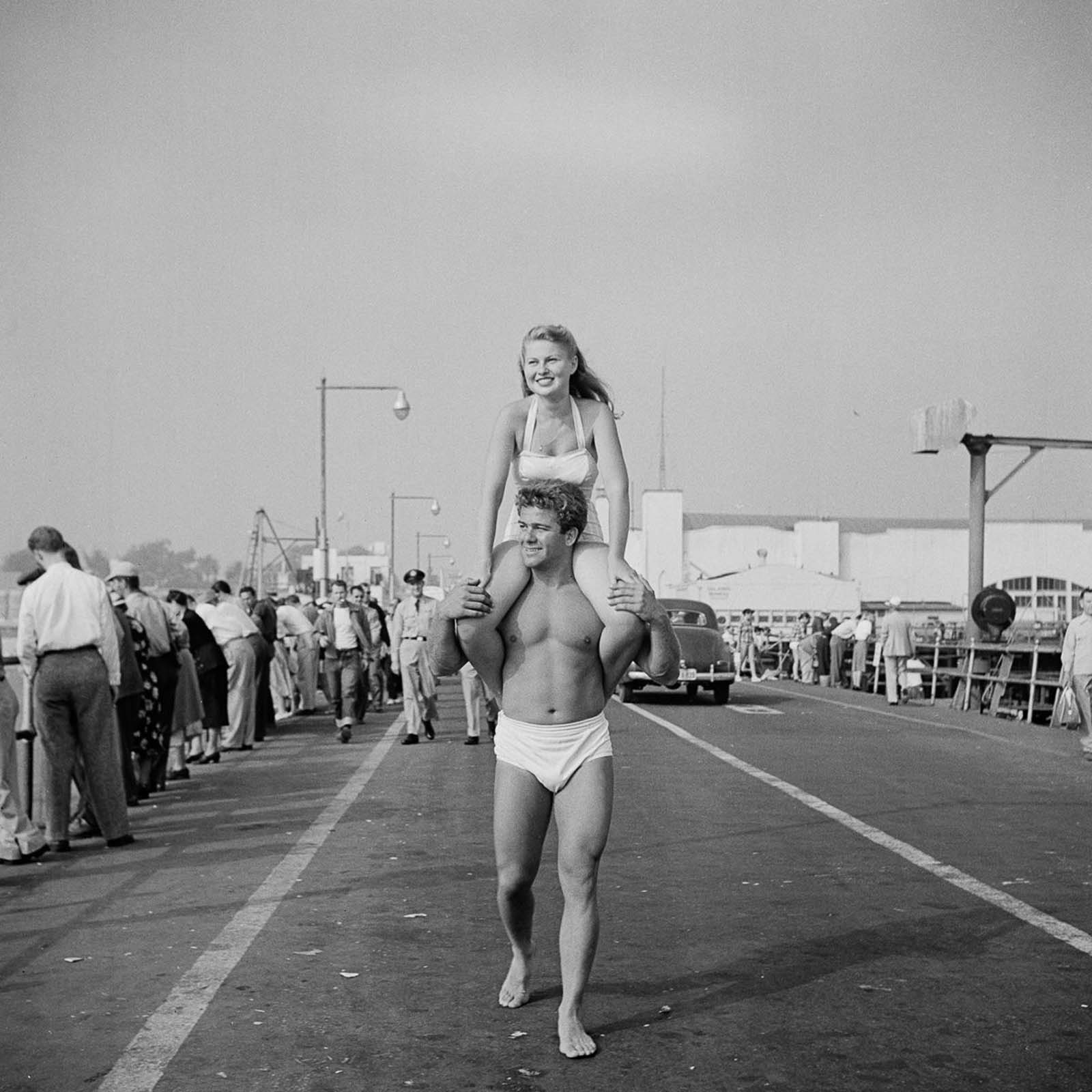 The same couple walking around the Muscle Beach.