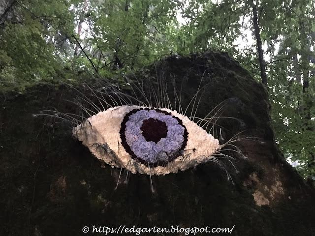 wachsames Auge mit  Pfauenfedern