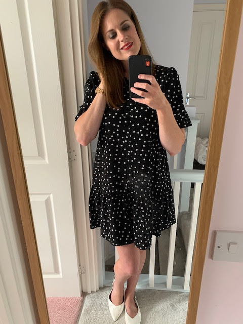 Woman in polka dot dress taking a mirror selfie