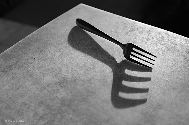 A Black and White Minimalist Photograph of a Fork and its long shadow, on a Marble table.
