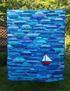 blue and aqua strips make ocean waves for the lone red sailboat made by Jennifer, Seafarer quilt pattern by QuiltFabication