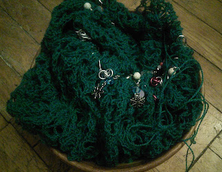 A lace shawl on a circular needle, sitting in a wooden yarn bowl.  The lace yarn is dyed to a deep blue-green, and there are many stitch markers along the circular needle.