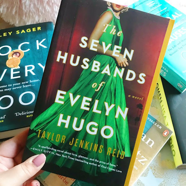 The Seven Husbands of Evelyn Hugo by Taylor Jenkins Reid held up over flatlay of other books