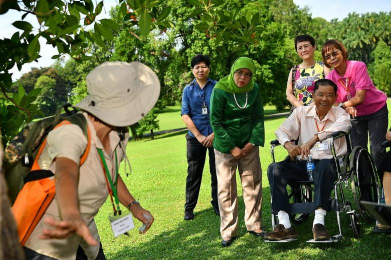 Some of the 44 guests from HCA Hospice Care enjoying a tour at the Istana garden with President Halimah Yacob (in green) yesterday.