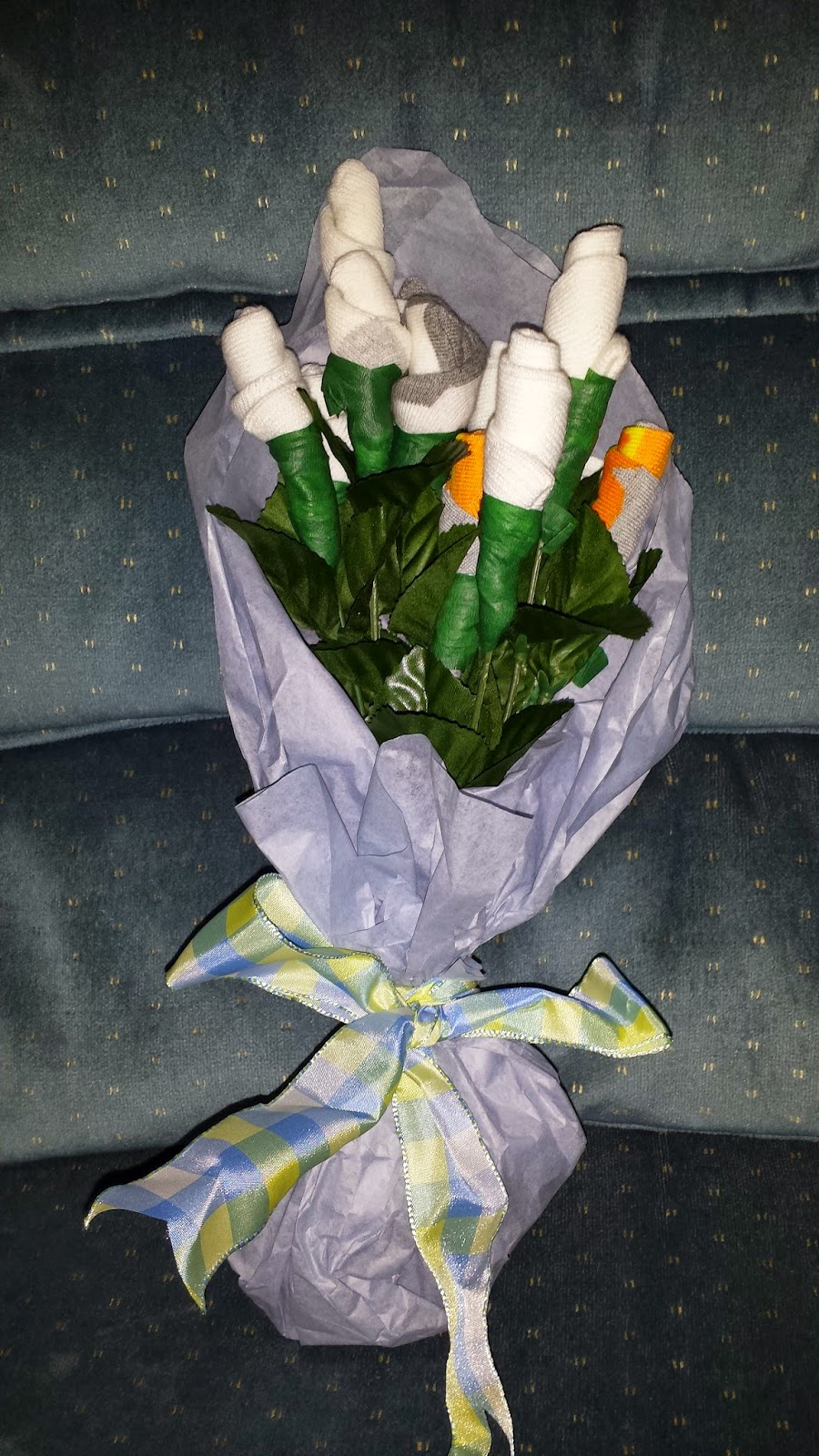 2 completed bouquets made from baby socks wrapped in tissue paper and tied with ribbon