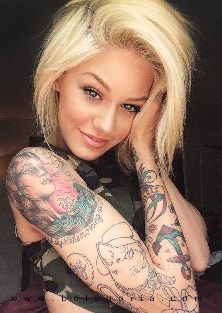 Vemos a una modelo rubia sonriendo, lleva tatuajes de moda