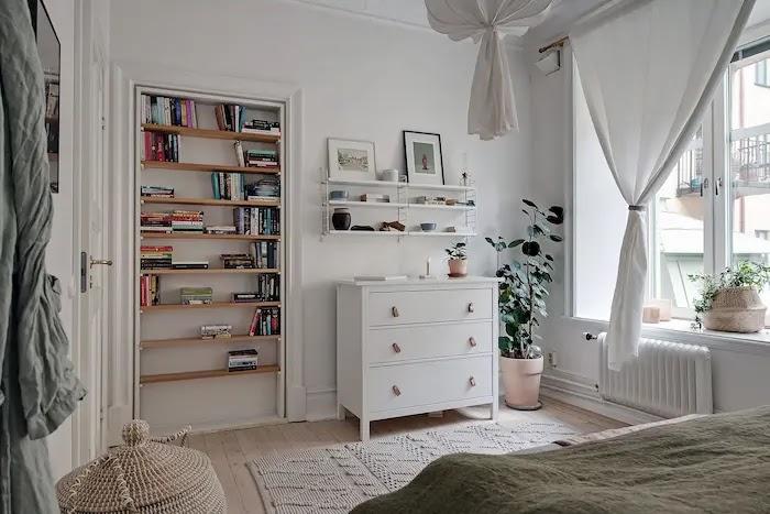 Dormitorio con librería en un hueco de la pared