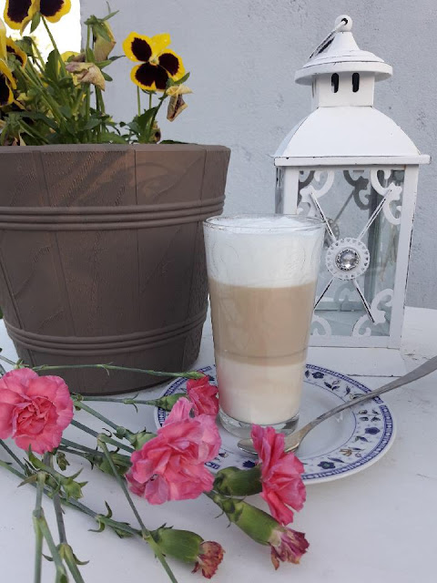 kawa latte machiato w ogrodzie przy lampie