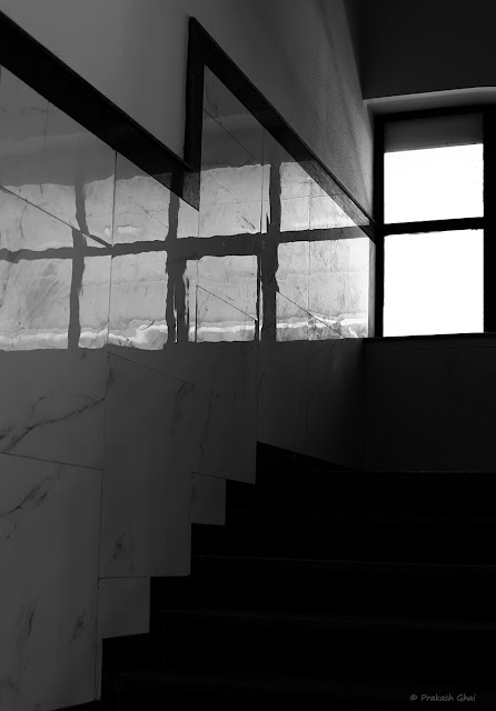 A Black and White Minimal Art Photograph of Light Coming through Two Window Panes at a Staircase of a Shopping Mall.