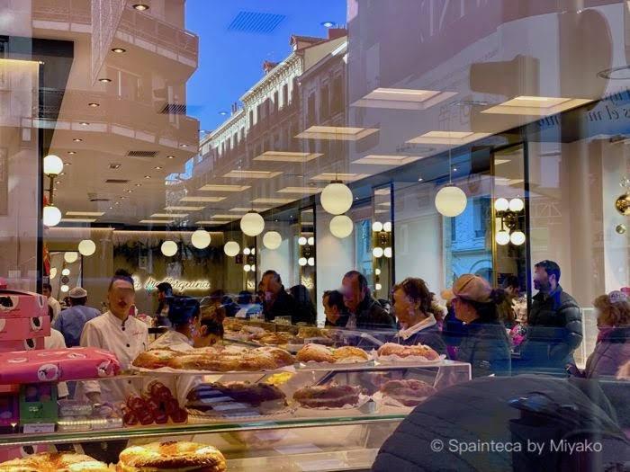 マドリードのラ・マヨルキナの店内で王様のケーキを買うスペイン人たち