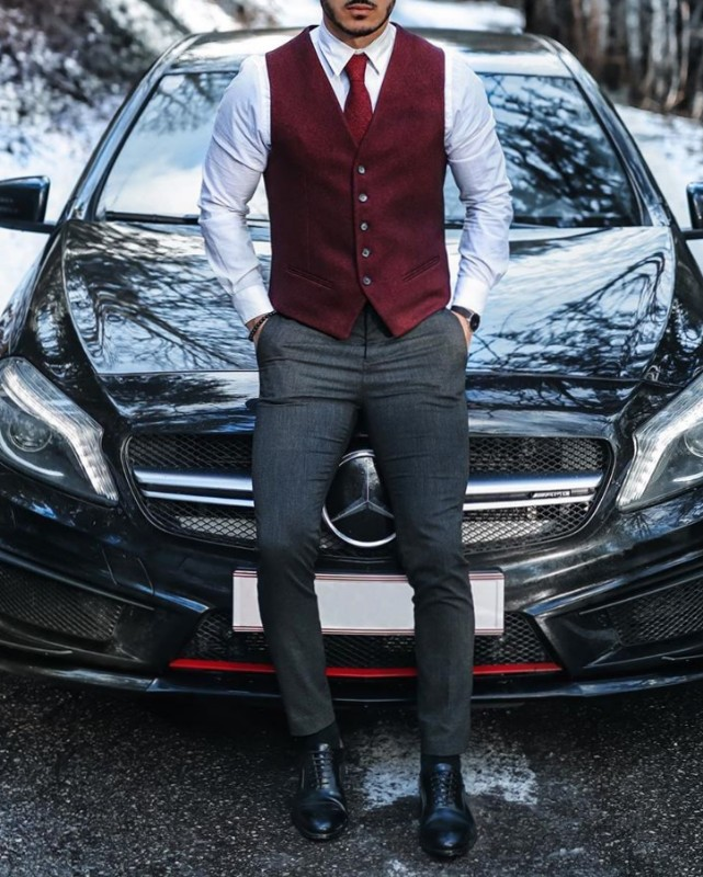 Maroon vest and shirt with grey trousers.
