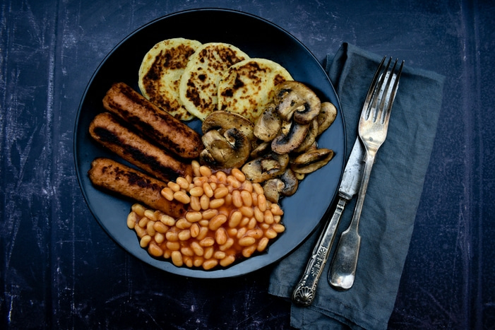 full cooked vegan breakfast - potato scones, veggie sausages, mushrooms and baked beans
