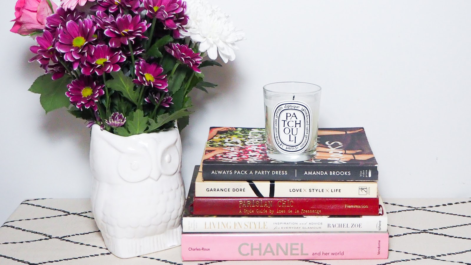 Diptyque Patchouli Candle with a vase of flowers and fashion books