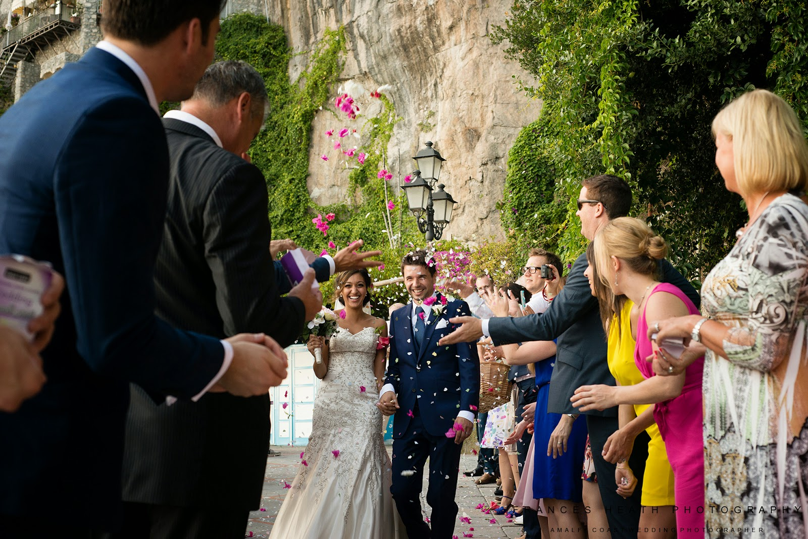 Wedding guests throw confetti at bride and groom in Positano