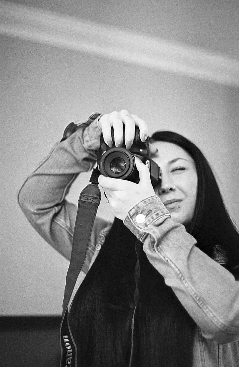 A black and white photo of a girl with long black hair, lip piercings and long nails wearing a denim jacket whilst taking a photo on a canon 70D in black and white. Photo is of myself, Jordanne lee