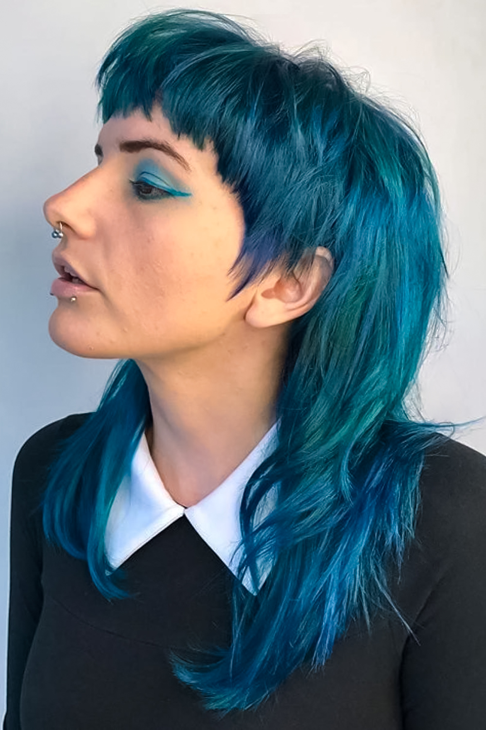woman with dyed edgy mullet haircut is posing on plain background
