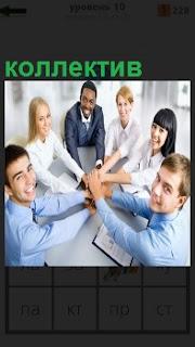 За столом коллектив молодых людей держащихся за руки друг друга