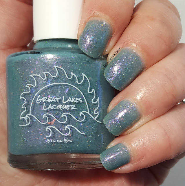 Blue-grey nail polish in a jelly finish with iridescent falkes and scattered holo glitter