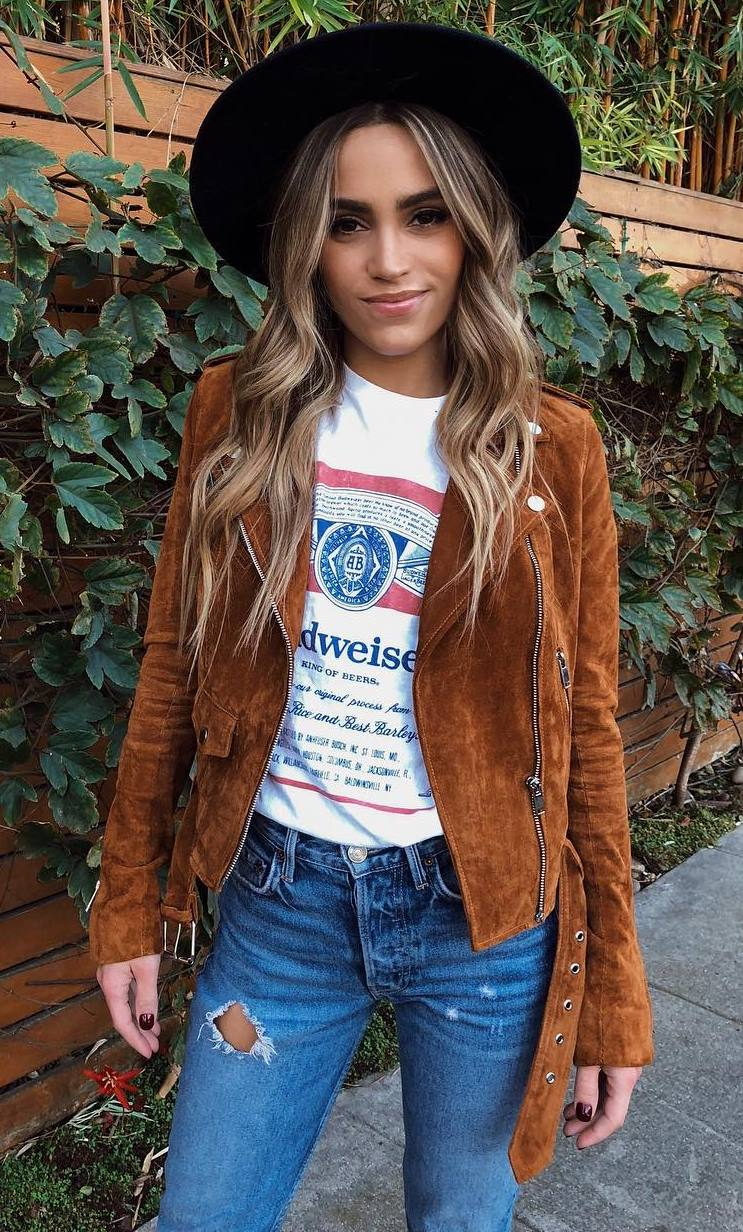 what to wear with a brown biker jacket : printed top + jeans + hat
