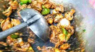 Stir frying chilli mushroom in wok with laddle