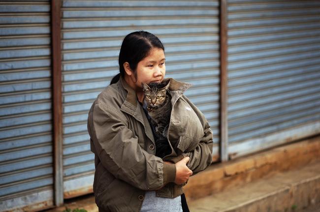 Тайская женщина в теплой куртке обнимает кота