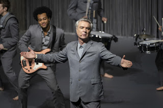 David Byrne in a grey suit on stage with band behind