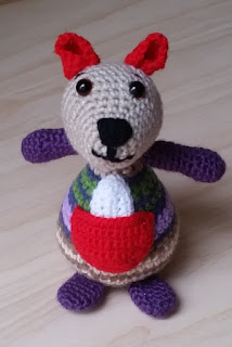 Hello! I am a crocheted kangaroo joey with a fawn face, dark facial features, red ears and pouch, purple limbs and a striped body with white chest.
