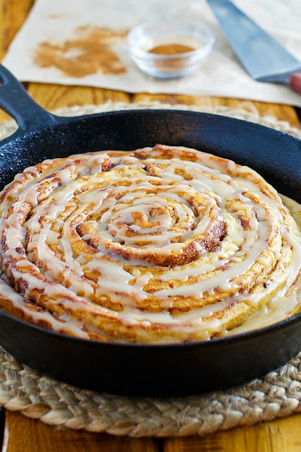 looking across the top of a fresh from the oven pumpkin spice skillet cinnamon roll with yummy maple brown butter glaze