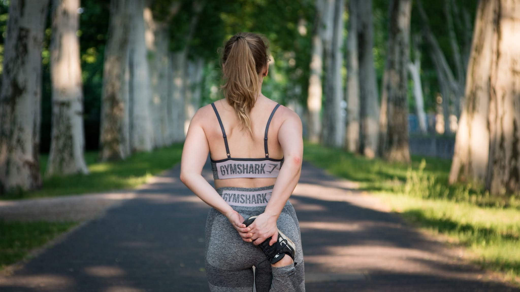右足を尻に上げて準備運動をする女性の後ろ姿