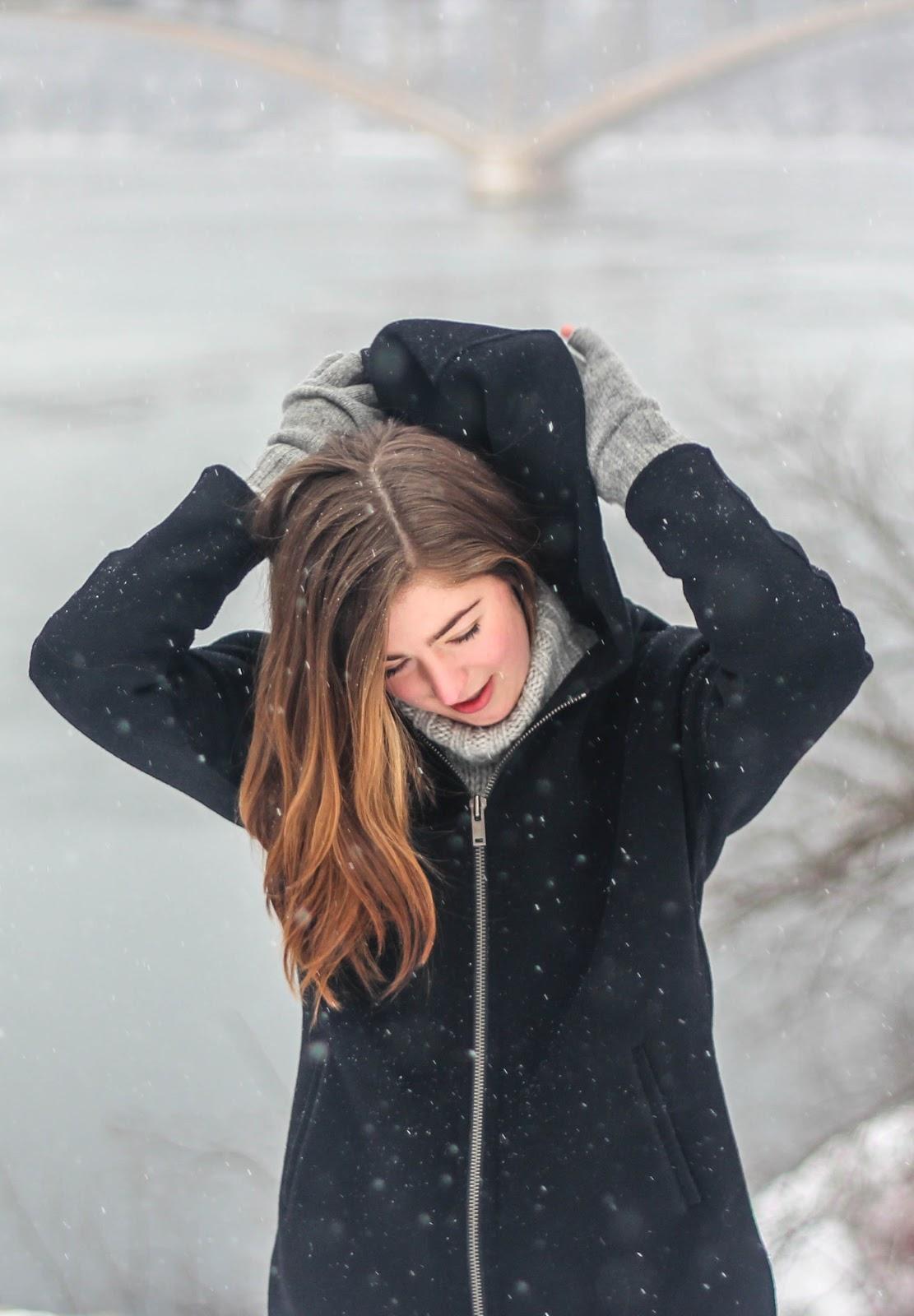 小雪が舞う中で頭を下げて紺色のコートのフードを両手で持ち上げる女性
