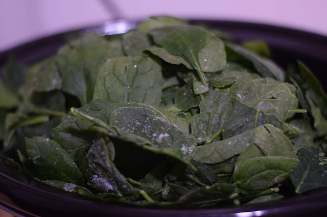 One bag of spinach being added to the slow cooker.