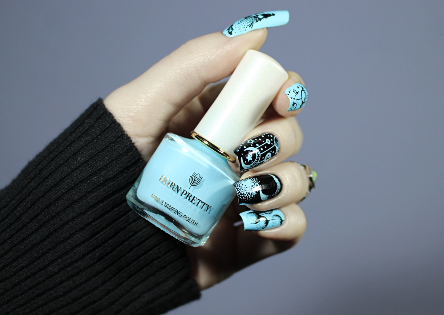 baby-blue and black nails with celestial designs on it