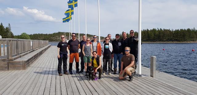 12 ihmistä ja 1 koira ryhmäkuvassa laiturilla, taustalla liehuu Ruotsin lippuja.