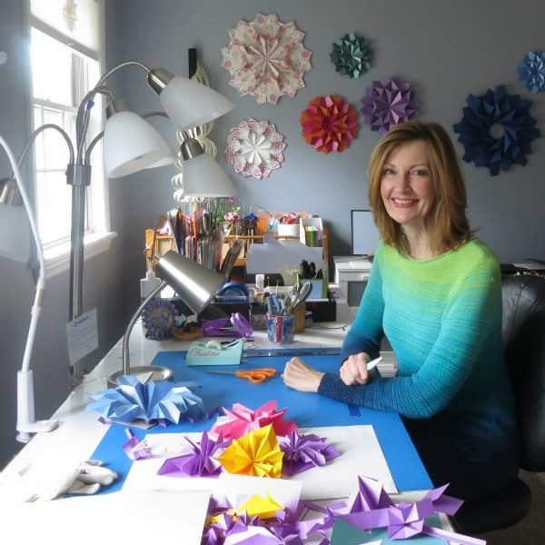 smiling woman seated at desk with paper craft supplies