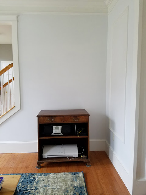 white room with foggy medallion rug and vintage bookcase cabinet