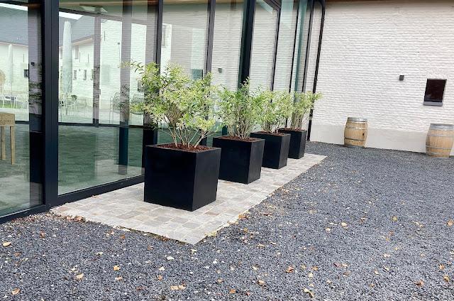 Grote witte of zwarte plantenbakken voor buiten op poten met klimrek op terras of binnen in beton polyester steen staal steigerhout of hout